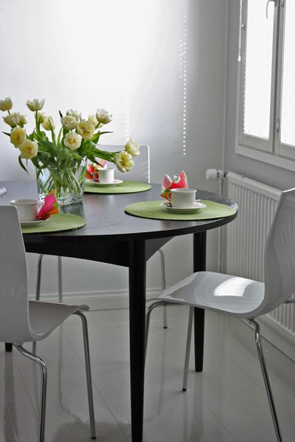 Musta pöytä ja valkoiset tuolit