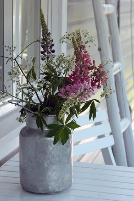 Vaihtuvat kukat ikkunan takana