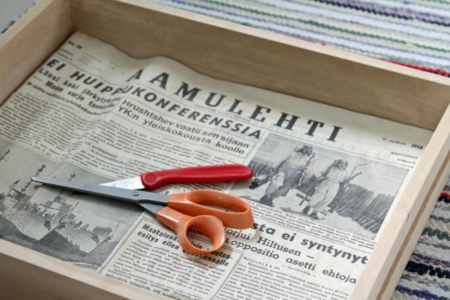 Sanomalehtipaperin sovitus hyllyn pohjalle
