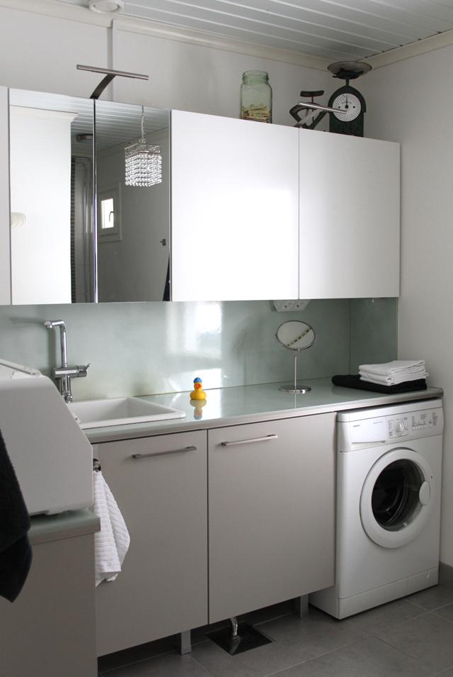 Kodinhoitohuone, valkoiset ja harmaat kaapit