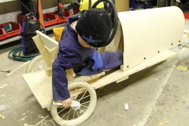 Pikkuapulainen mäkiautoa tekemässä